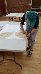 Student pinning a dress pattern to fabric ready to cut out